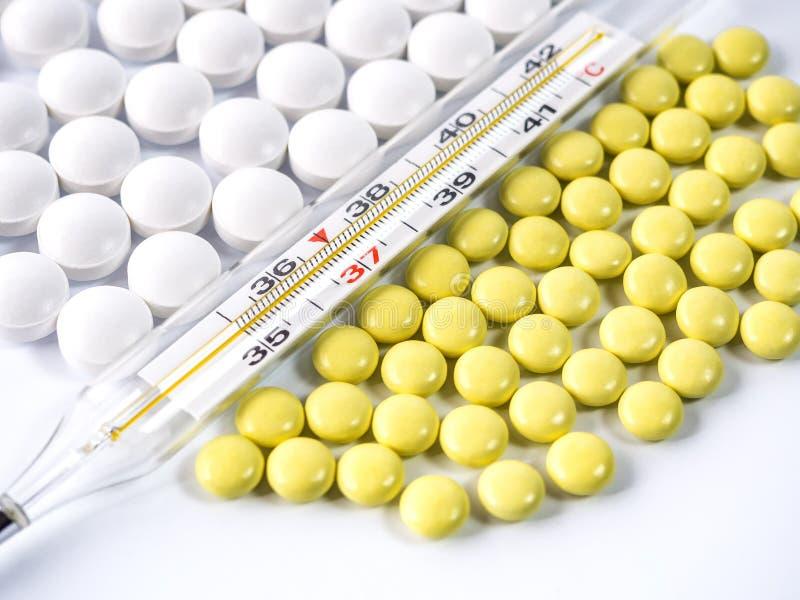 在说谎在白色背景的黄色和白色片剂的温度计 免版税库存照片
