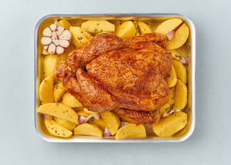在调味汁的整个用卤汁泡的鸡用在烘烤的盘的未加工的土豆 免版税图库摄影