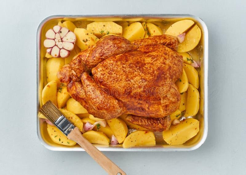 在调味汁的整个用卤汁泡的鸡用未加工的土豆,与在烘烤的盘的刷子,顶视图 免版税库存图片