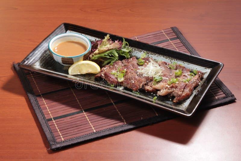 在调味汁的油煎的牛肉烹调 库存图片