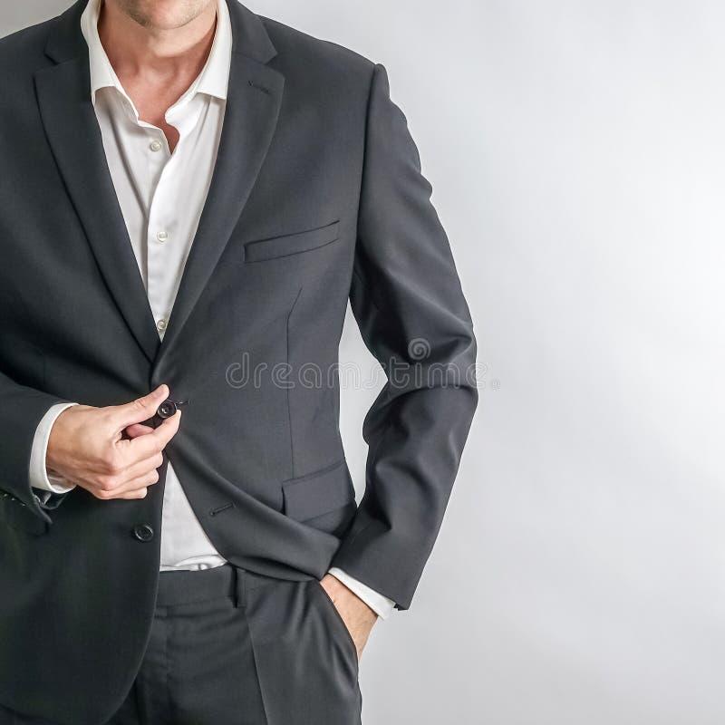 在调整他的夹克的黑衣服的穿着体面的商人 图库摄影
