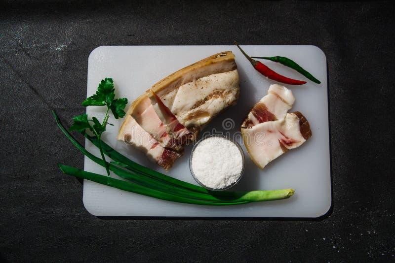 在调盐器上用药草和盐装饰的白板上,用猪油切成薄片,再加上一层肉 图库摄影