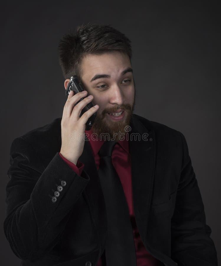 在谈话的愉快的商人通过电话 免版税图库摄影