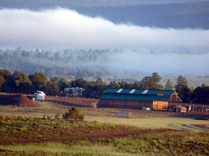 在谷仓后的低云大农场的 免版税库存照片