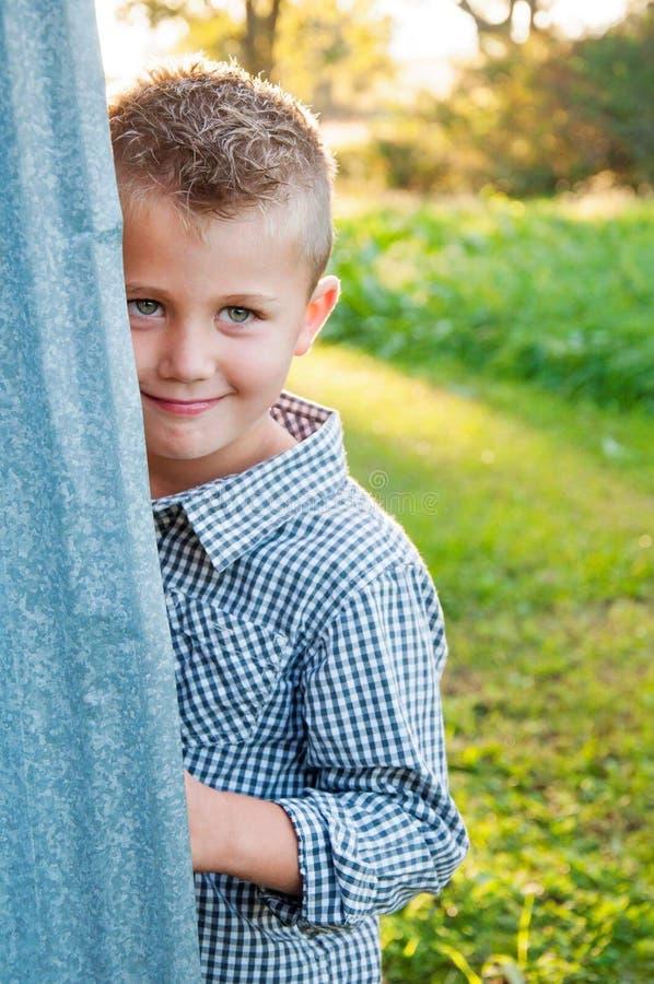 在谷仓后的害羞的男孩 图库摄影