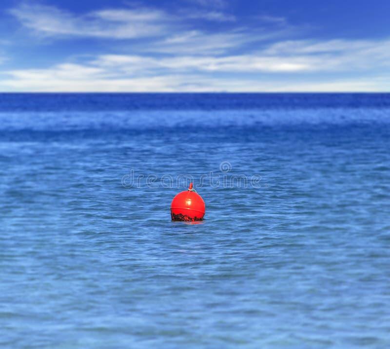 在象紧急标志的蓝色海洋漂浮帆船的 免版税库存照片