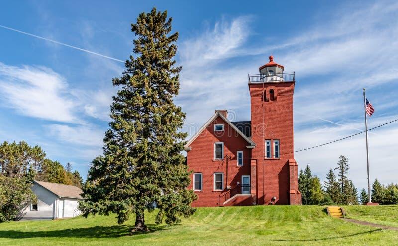在象草的草坪小山的两个港口灯塔  免版税图库摄影