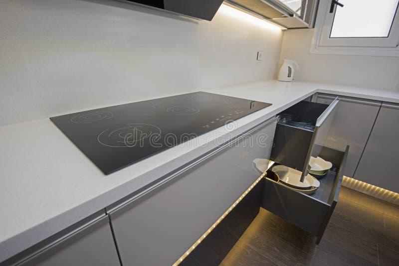 在豪华公寓的现代厨房烹饪器材滚刀设计 免版税库存图片