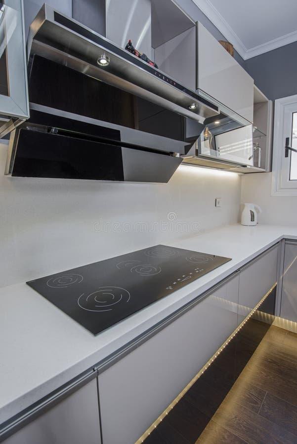 在豪华公寓的现代厨房烹饪器材设计 图库摄影