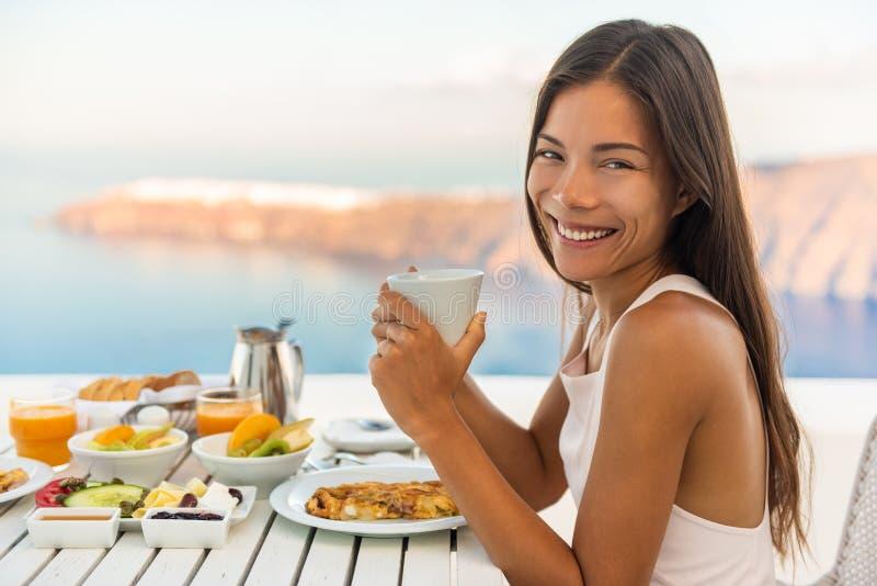 在豪华旅游酒店餐厅享用早午餐的早餐女性,在户外阳台上享用地中海美景的咖啡杯 免版税库存照片