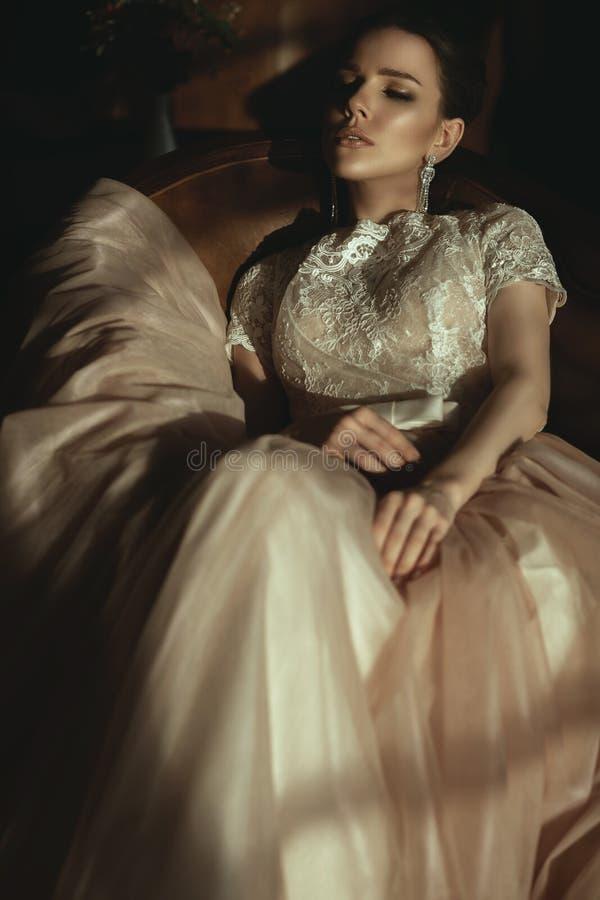 在豪华松的礼服的美好的模型有遮掩的在扶手椅子放松的裙子坐 免版税库存照片
