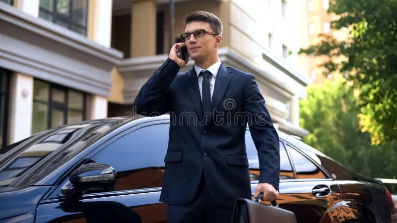 在豪华汽车附近的商人身分谈话在智能手机,怏怏不乐对于新闻 免版税库存照片