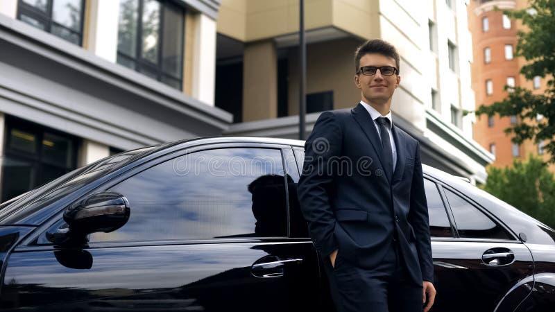 在豪华汽车附近的微笑的不动产经理身分在成功的成交以后 免版税库存图片