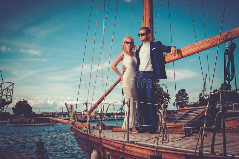 在豪华游艇的时髦的富裕的夫妇 图库摄影