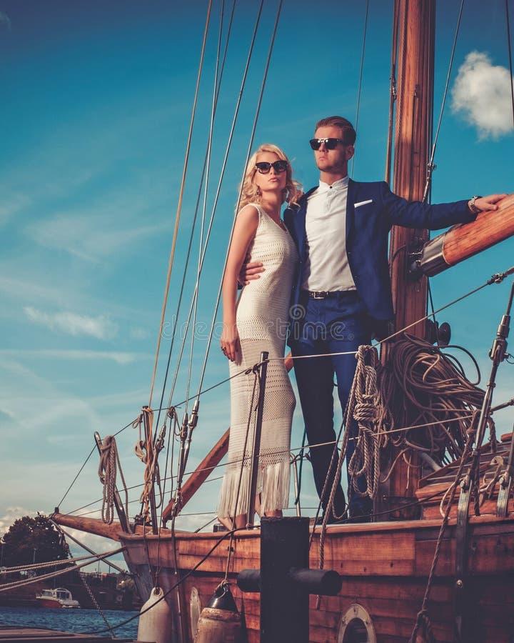 在豪华游艇的时髦的富裕的夫妇 免版税库存图片