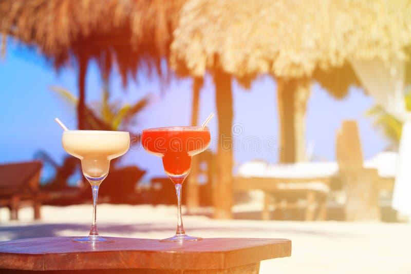 在豪华热带沙子海滩的两个鸡尾酒 免版税库存照片