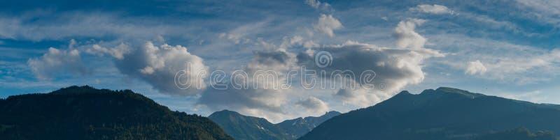 在豪华的绿色森林里报道的山风景全景视图在一传神天空和cloudscape下 图库摄影