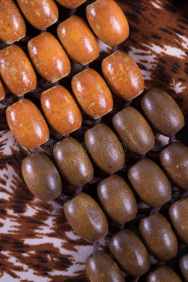 在豹子的橙色和棕色木小珠打印背景的布料 免版税图库摄影
