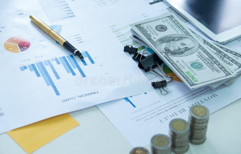 在财务图文件的笔与硬币和美元 免版税图库摄影