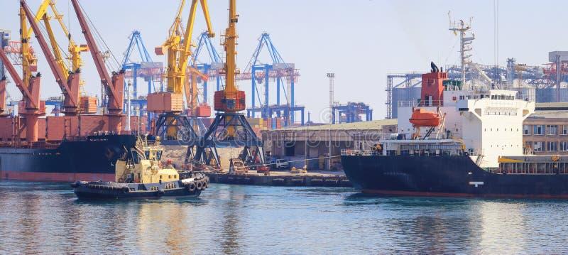 在货船弓的拖轮,协助船操纵在口岸 免版税图库摄影