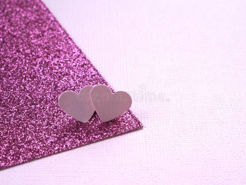 在质地纸和明亮的桃红色纸板抽象背景的两浅粉红色的心脏与闪烁 宏指令 免版税库存图片