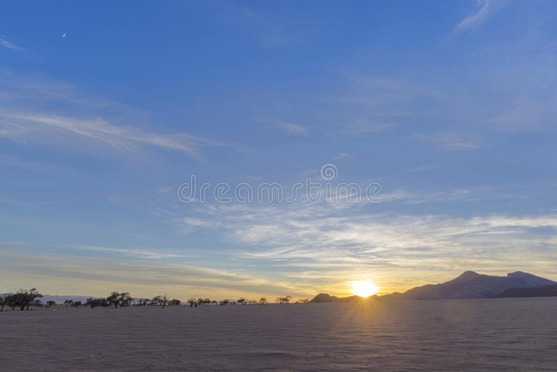 在贫瘠含沙区域的日出 免版税库存照片
