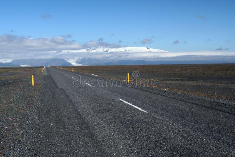 在贫瘠宽风景的不尽的平直的柏油路与黄色路旁标志到无处,冰岛里 免版税库存图片