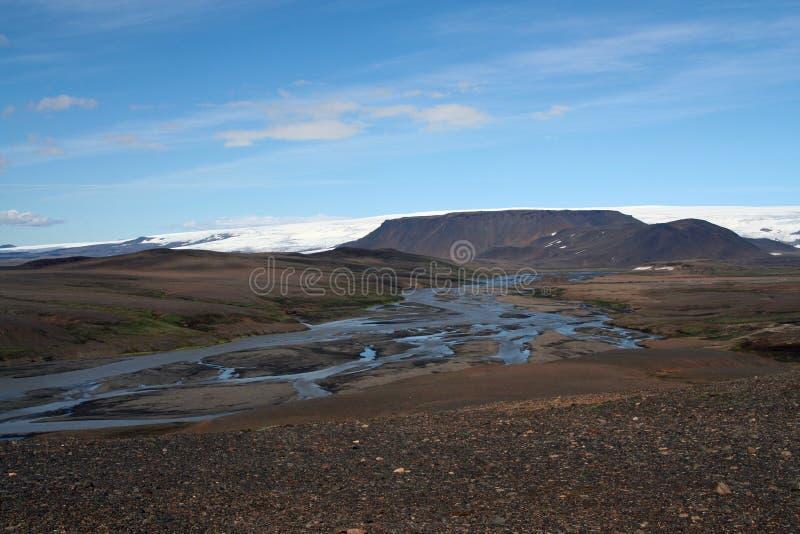 在贫瘠废黑平原的看法与在雪的小河部分加盖了在天际-冰岛的山 免版税库存照片