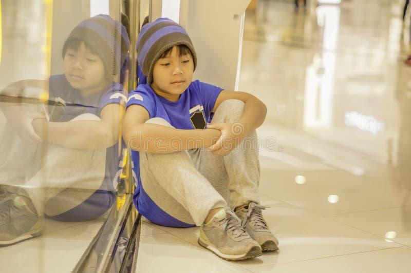 在购物中心哀伤和注重的亚洲男孩开会,丢失的孩子的概念从父母的 免版税图库摄影