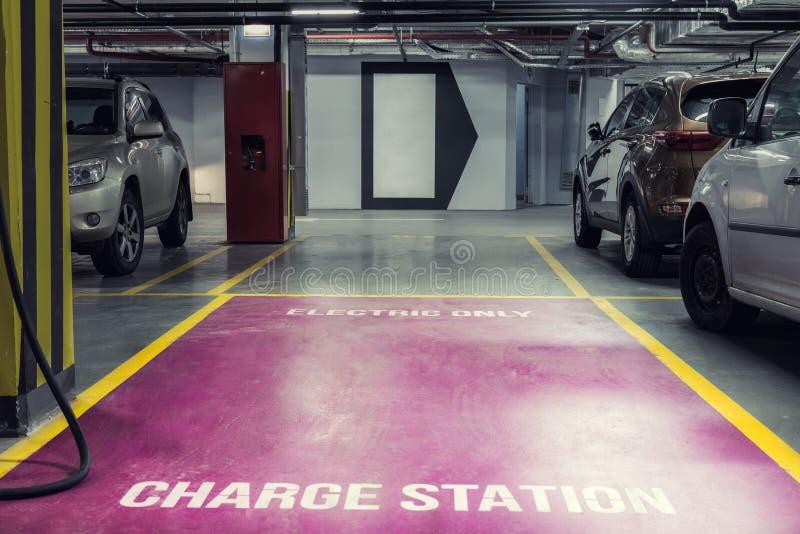 在购物中心或办公楼地下室内停车处的电车充电站  环境的后备的停车场 库存照片
