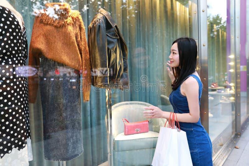 在购物中心的愉快的亚洲中国东部东方年轻时髦妇女女孩购物与袋子看在街道城市的购物窗口 免版税库存照片