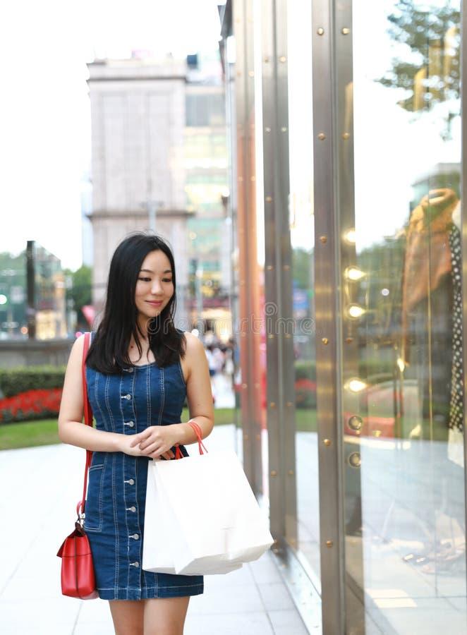 在购物中心的愉快的亚洲中国东部东方年轻时髦妇女女孩购物与袋子看在街道城市的购物窗口 图库摄影