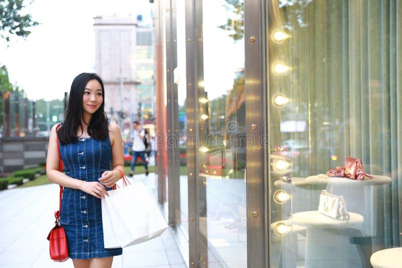 在购物中心的愉快的亚洲中国东部东方年轻时髦妇女女孩购物与袋子看在街道城市的购物窗口 免版税库存图片