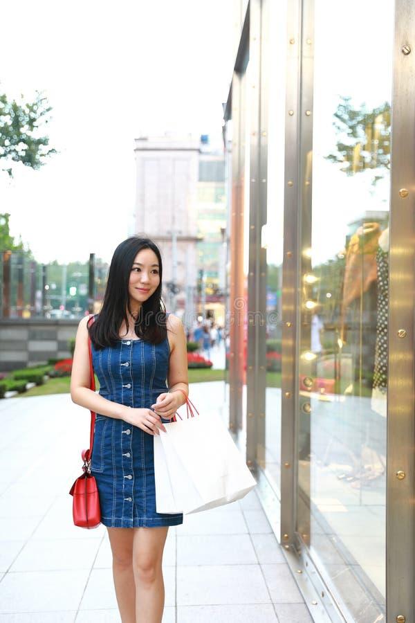 在购物中心的愉快的亚洲中国东部东方年轻时髦妇女女孩购物与袋子看在街道城市的购物窗口 库存图片