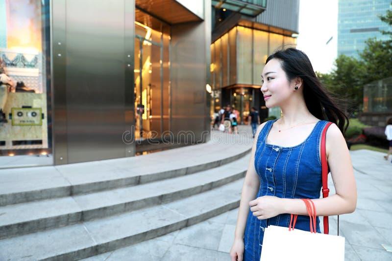 在购物中心的愉快的亚洲中国东部东方年轻时髦妇女女孩购物有在街道城市的袋子购物的窗口背景 免版税图库摄影