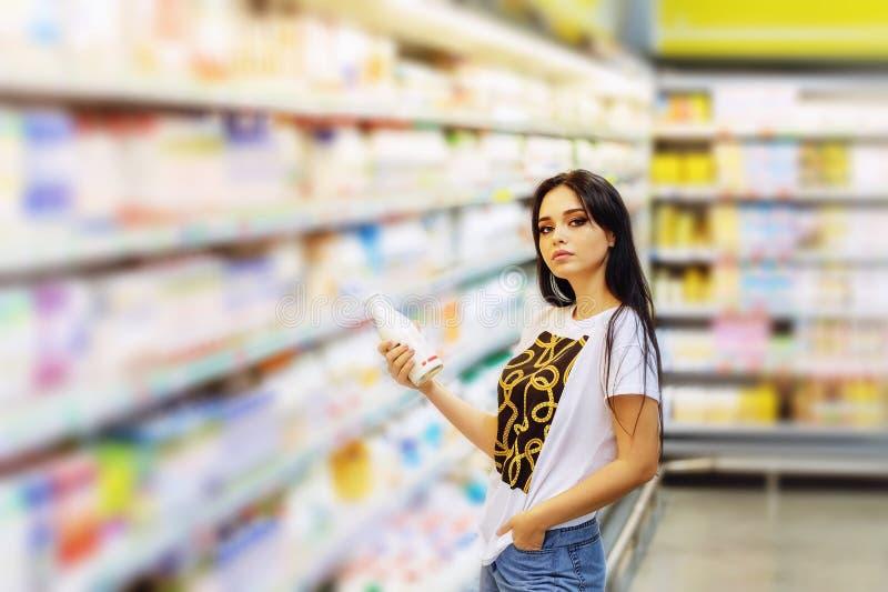 在购物中心里摆着食物的搁架背景上,年轻美女手里拿着一瓶牛奶 免版税库存照片