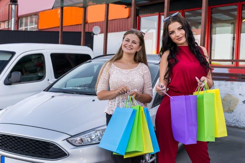 在购物的愉快的朋友在购物中心附近的停车处以后 库存照片