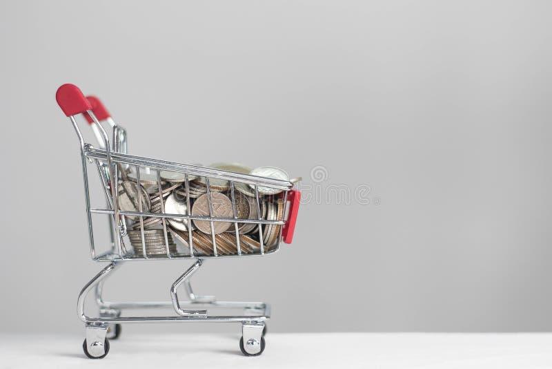 在购物车的硬币在白色背景 库存图片