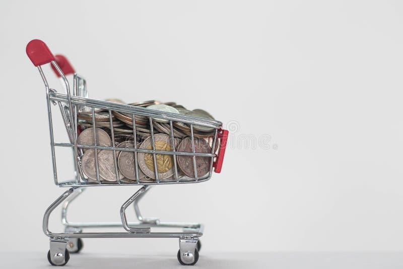 在购物车的硬币在白色背景 免版税库存照片