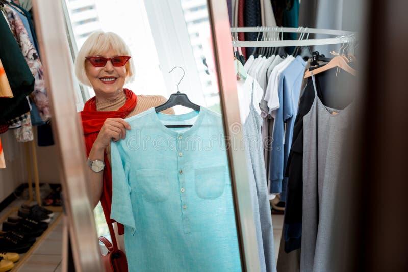 在购物镜子前面的时髦的年长妇女 免版税库存图片
