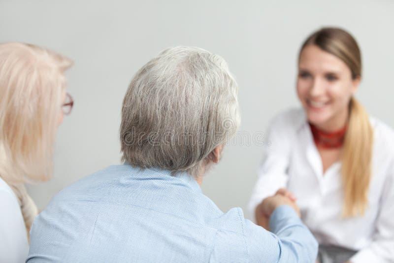 在资深夫妇握手顾问或医护人员的背面图 免版税图库摄影