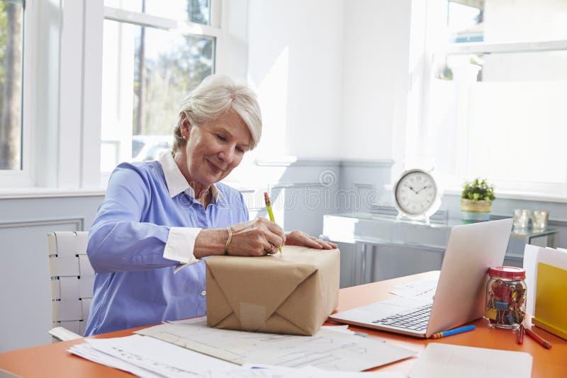 在资深的妇女在家邮寄的包裹写地址 免版税库存图片