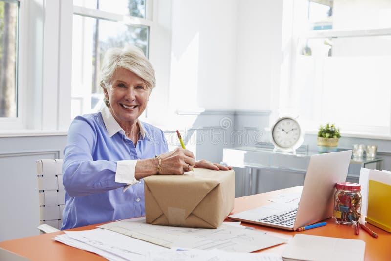 在资深的妇女在家邮寄的包裹写地址 图库摄影