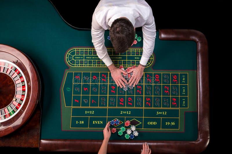 在赌博娱乐场供以人员演奏轮盘赌的副主持人和妇女在桌上 顶视图在与磁带的轮盘赌选材台上 免版税库存照片