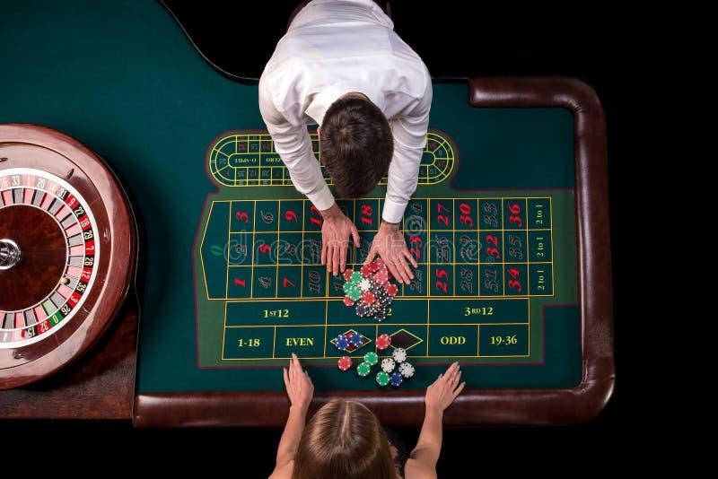 在赌博娱乐场供以人员演奏轮盘赌的副主持人和妇女在桌上 顶视图在与磁带的轮盘赌选材台上 免版税库存图片