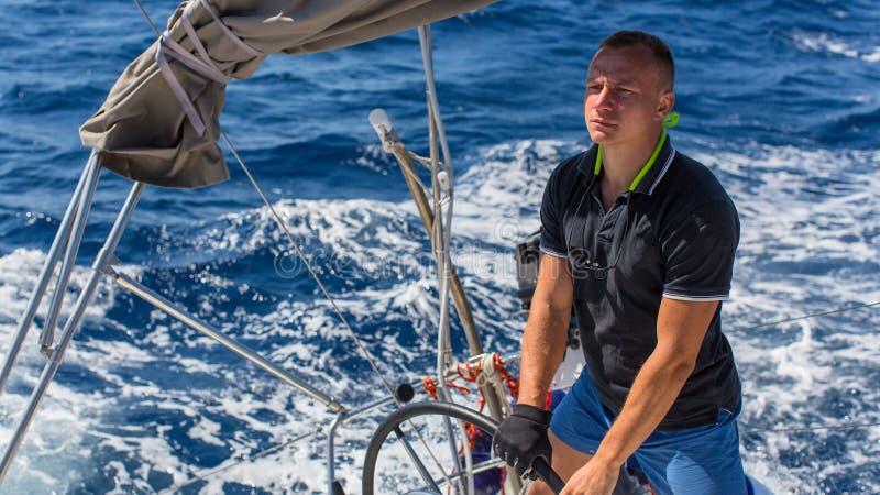 在赛艇期间,一个年轻人船长控制航行游艇的运动 免版税库存照片