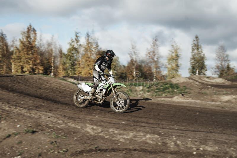 在赛马跑道的摩托车越野赛司机 免版税库存图片
