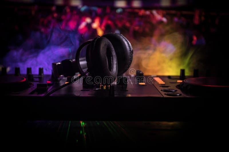 在赞成dj控制器选择聚焦  DJ慰问节目播音员混合的书桌在音乐党在有色的迪斯科光的夜总会 免版税库存图片