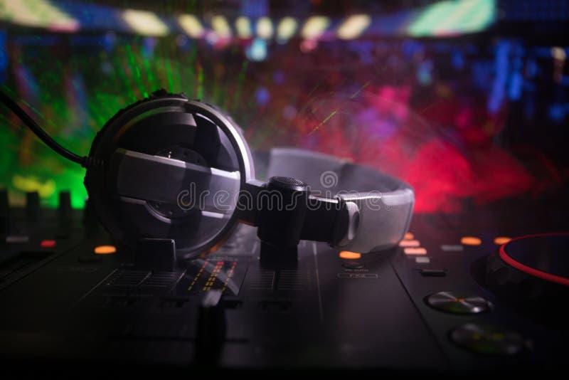在赞成dj控制器选择聚焦  DJ慰问节目播音员混合的书桌在音乐党在有色的迪斯科光的夜总会 免版税库存照片