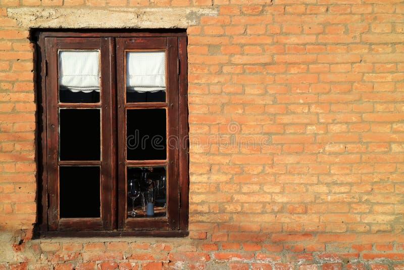 在赤土陶器砖墙上的黑褐色木窗口在阳光下 库存照片